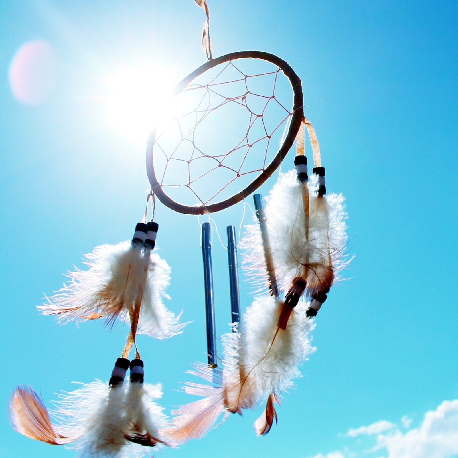 Photo of a dream catcher with a blue sky background.